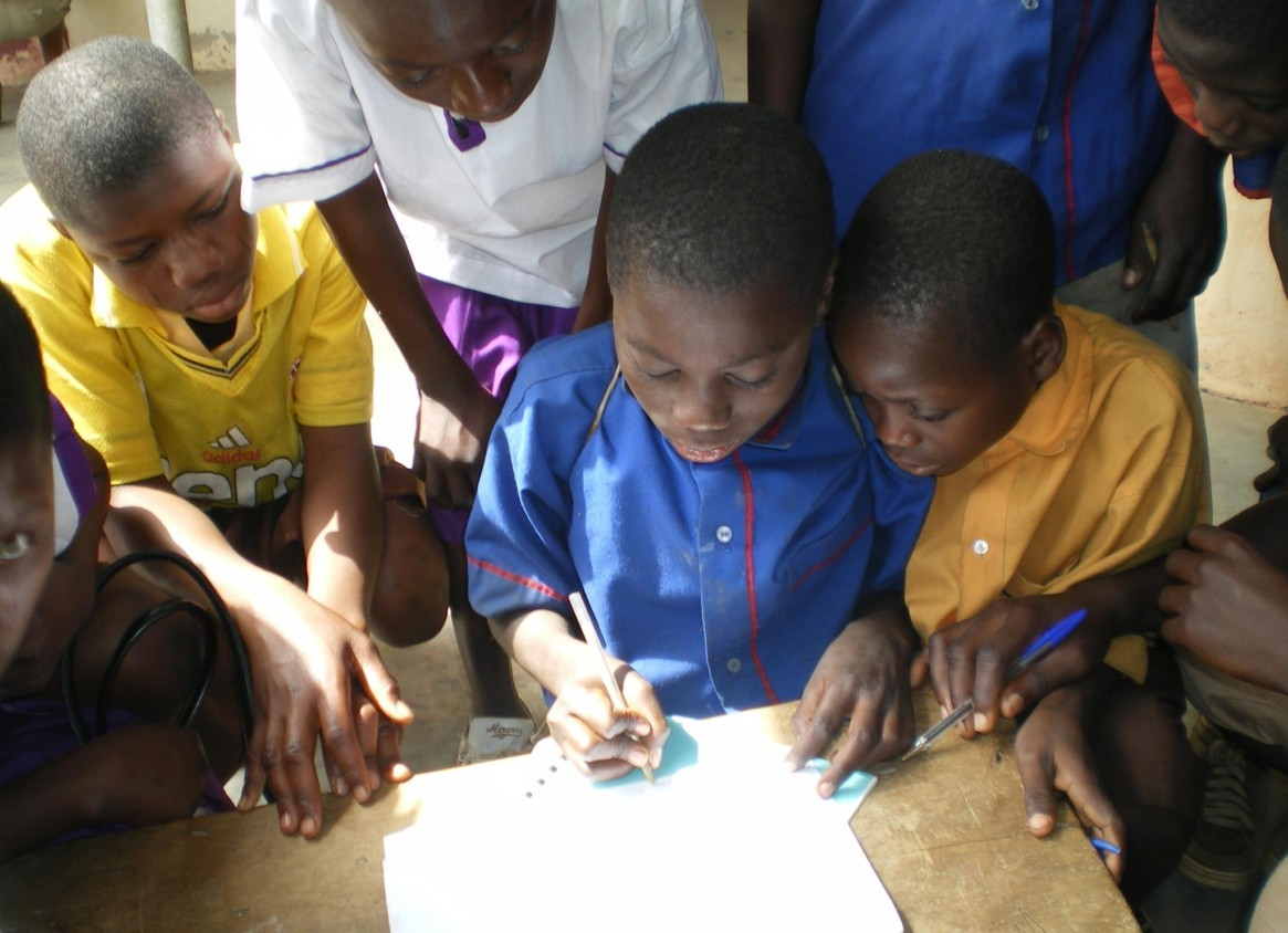 Photo of children with Youth Alive, Ghana writing in the classroom