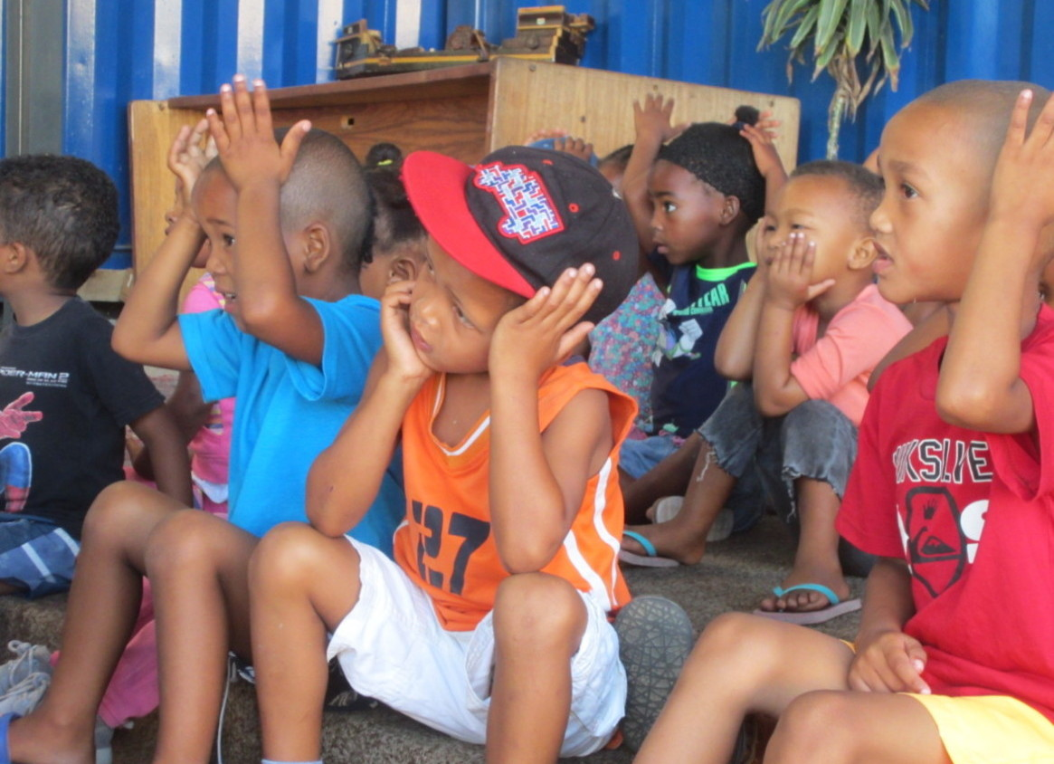 Photo of children in Uitsig doing actions to songs at the container school