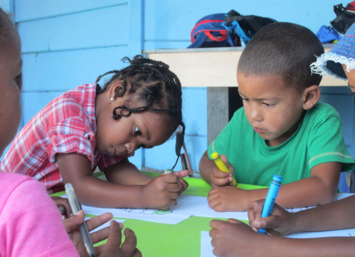 Photo of 2 children in Uitsig colouring in at the container school