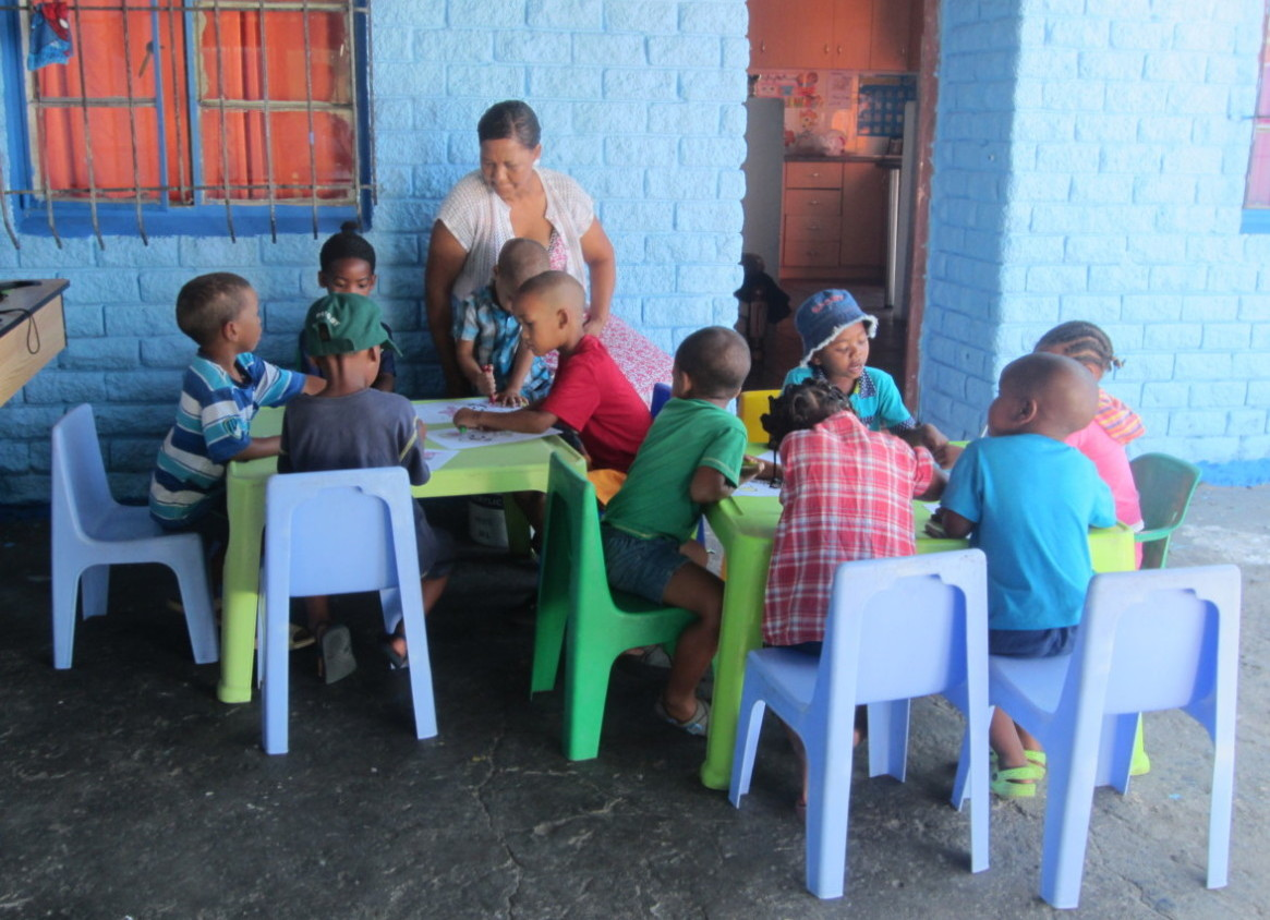 Photo of children in Uitsig at one of the home school units sitting at tables colouring pictures