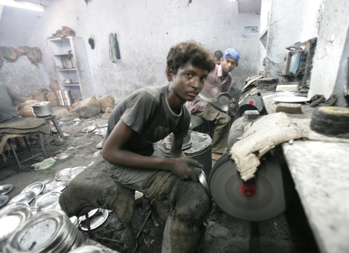 Photo of young boy working making metal plates in Tamil Nadu