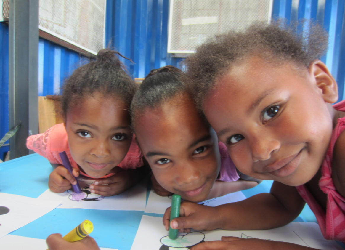 Photo of 3 girls at New Life, South Africa colouring pictures