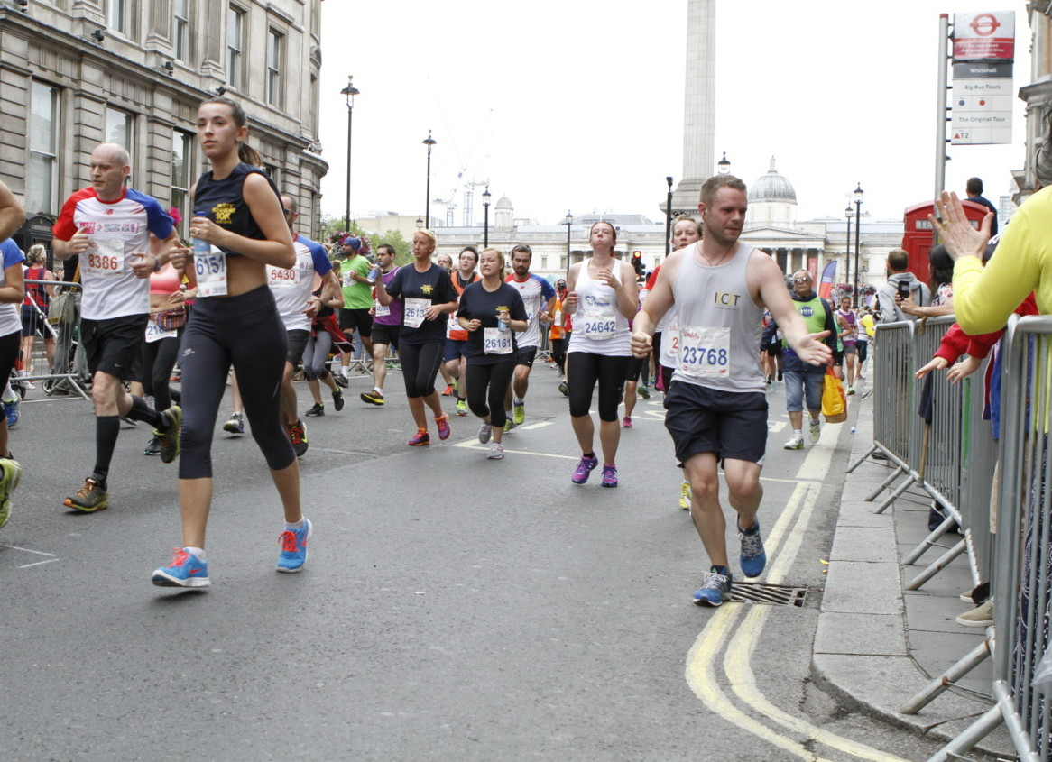 Photo of International Children's Trust runner giving a high five to a child as he runs from Trafalgar Square