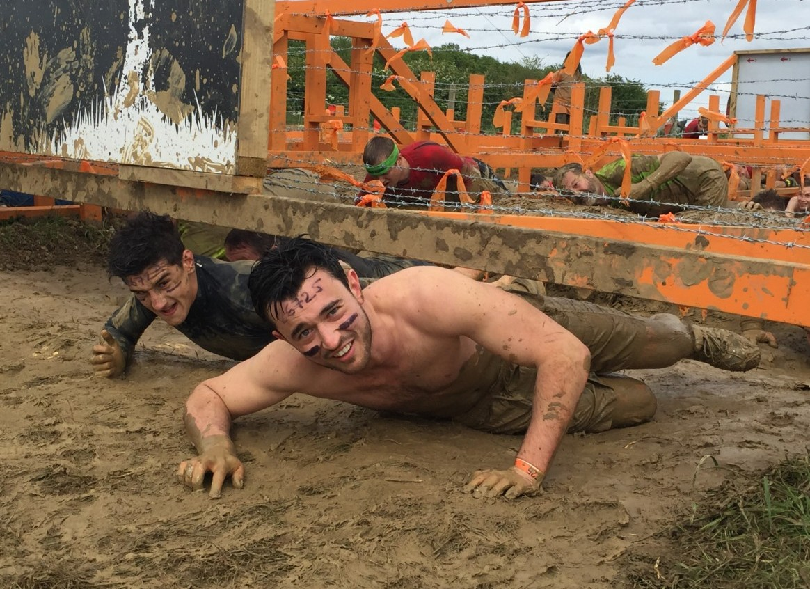Photo of Jack and Richard crawling in the mud under barbed wire at Tough Mudder