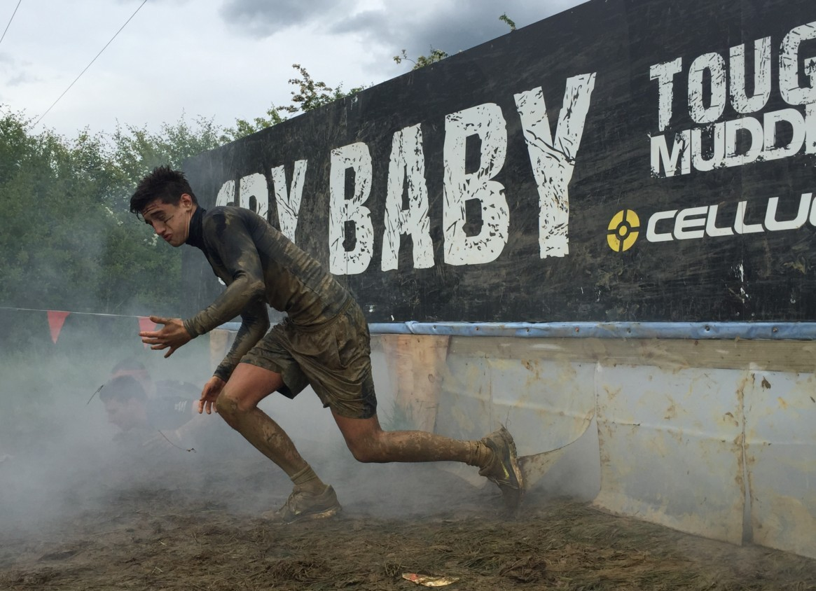 Photo of Richard running out of a smokey obstacle at Tough Mudder
