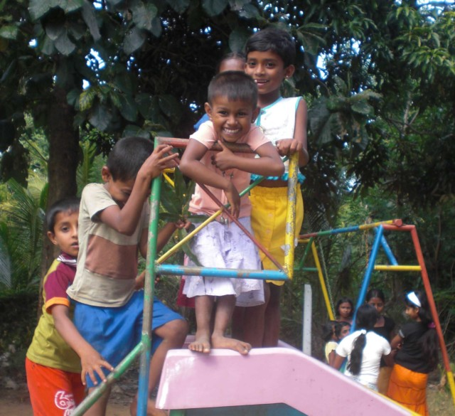 Photo of children on the top of a slide at the playpark with SERVE, Sri Lanka