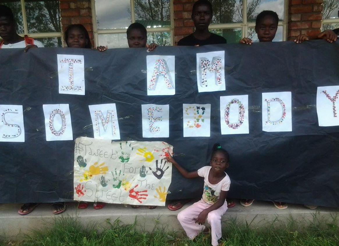 Photo of children at Chiedza, Zimbabwe holding their fingerprint artwork for the I Am Somebody campaign.