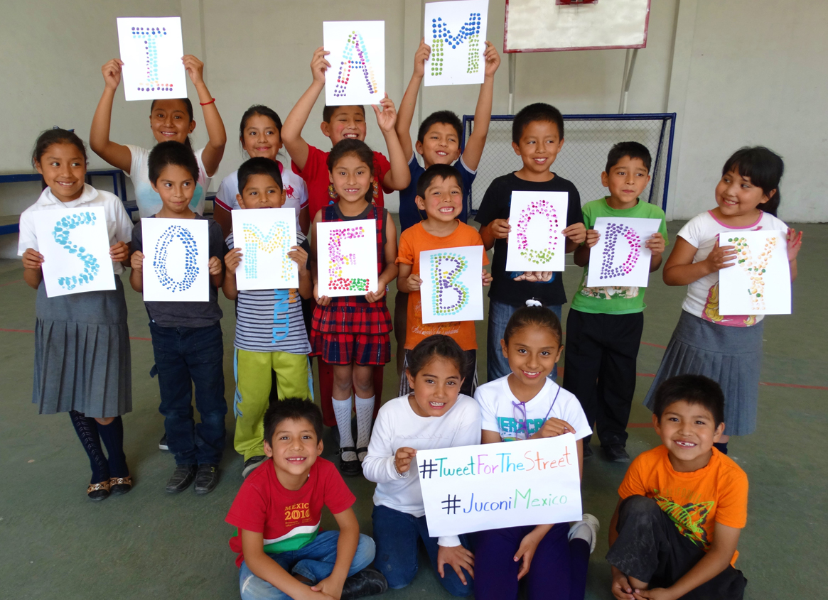 Photo of children at JUCONI Mexico holding their fingerprint artwork for the I Am Somebody campaign.