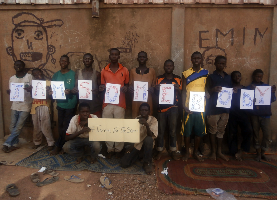 Photo of children at Keoogo, Burkina Faso holding their fingerprint artwork for the I Am Somebody campaign.