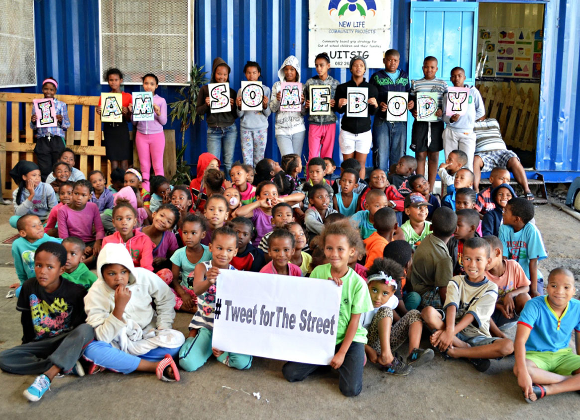Photo of children at New Life, South Africa holding their fingerprint artwork for the I Am Somebody campaign.