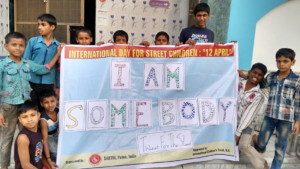 Photo of children working with SARTHI in Patna, India holding a banner with fingerprint artwork for the I Am Somebody campaign.