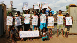 Photo of children working with SERVE, Sri Lanka holding their fingerprint artwork for the I Am Somebody campaign.
